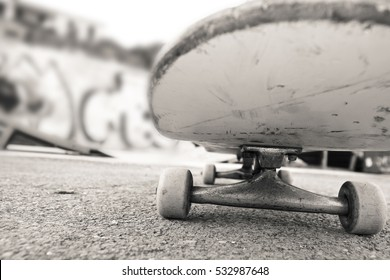 skateboard photographed from the front you can see wheels and the metal truck