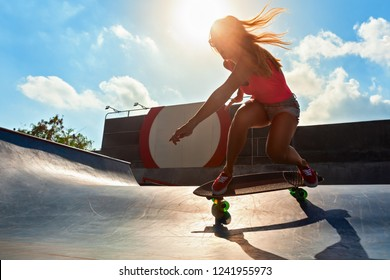 Skateboarder in action. Black silhouette of young woman making trick on surf skate in skatepark on sky with sun background. Street culture, skateboard riding lessons. Weekend recreational activities.