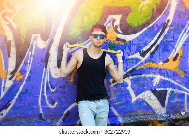 Skateboarder with black cap and sunglasses in front of graffiti wall.