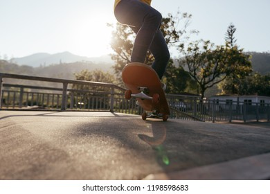 Skateboarder doing ollie at skatepark ramp