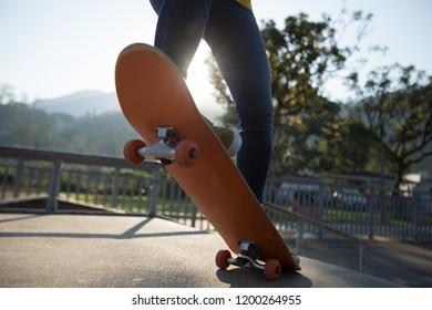 Skateboarder doing ollie at skatepark ramp