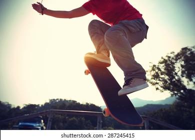 skateboarder doing a ollie at skatepark,vintage effect