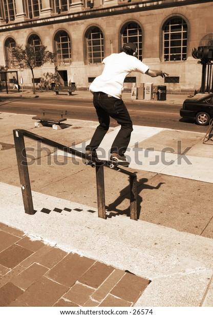Skateboarder doing a railslide.