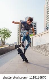 Skateboarder doing a skateboard trick ollie on the street of a city