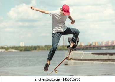 Skateboarder doing a trick at the city's street in sunny day. Young man in sneakers and cap riding and longboarding on the asphalt. Concept of leisure activity, sport, extreme, hobby and motion.