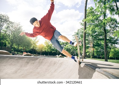 Skateboarder driving his board in a skate park - Young man doing a trick with his skate