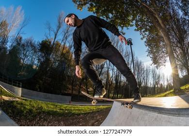 Skateboarder dropring a ramp at sunset at the local skatepark.