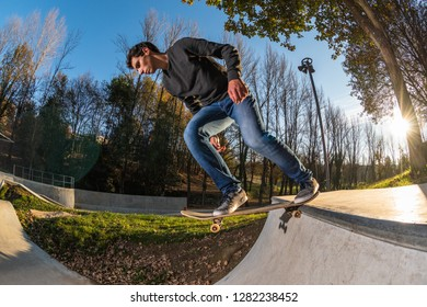Skateboarder dropring a ramp at sunset at the local skatepark.