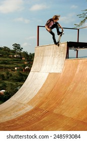 A skateboarder executes a radical move on a wooden half-pipe in Inanda Valley, KwaZulu-Natal, South Africa.