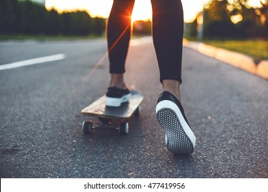 Skateboarder girl's legs starts ride in front of the sun. Back bottom view