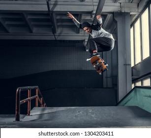 Skateboarder jumping high on mini ramp at skate park indoor.