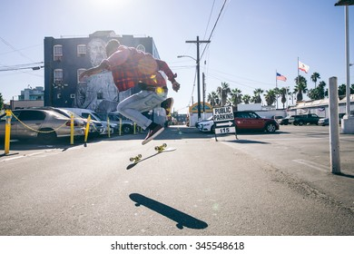 Skateboarder jumping with his skateboard on the streets - Young man attempting a trick with his skate