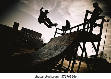 Skateboarder jumping on a ramp. Backlight makes dark silhouettes.