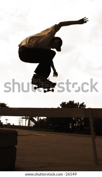 Skateboarder jumping over a barrier.  (ollie)