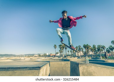 Skateboarder jumping over a gap in a skate park - Young man attempting a trick with his skate