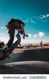 Skateboarder jumping in skate park bowl at Venice skatepark