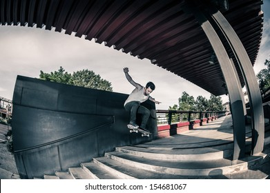 Skateboarder jumping stairs in the street.