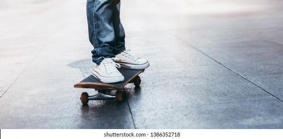 Skateboarder legs riding skateboard on city street