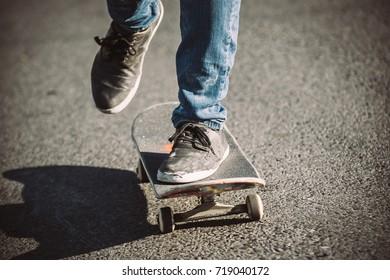Skateboarder legs riding skateboard on the street. Close up