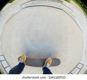 skateboarder legs riding skateboard at skatepark