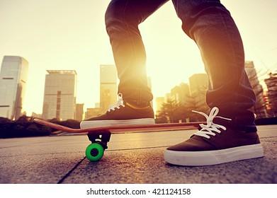 skateboarder legs skateboarding at sunrise city