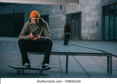 skateboarder in modern streetwear sitting on bench and using smartphone