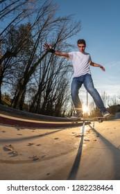 Skateboarder on a board slide at sunset at the local skatepark.