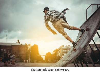 Skateboarder on a grind with dark clouds background at the local skate park, at sunset