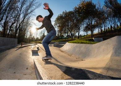 Skateboarder on a grind at sunset at the local skatepark.