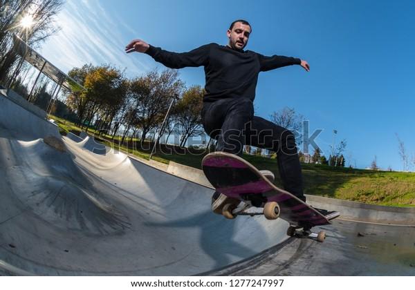 Skateboarder on a grind at sunset at the local skatepark.
