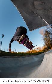Skateboarder on a melon backside grab at sunset at the local skatepark.