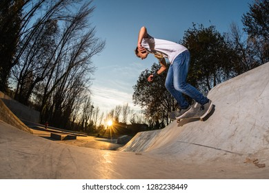 Skateboarder on wall turn at sunset at the local skatepark.