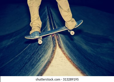 skateboarder performing a rail slide in the middle of the board in a skate park with a shallow depth of field with a toned retro instagram filter