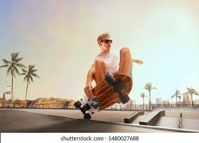 Skateboarder is performing tricks in skatepark on sunset.