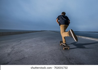 Skateboarder pushing on a concrete pavement along the harbour.