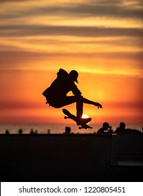 Skateboarder silhouetted against colorful sunset doing aerial trick