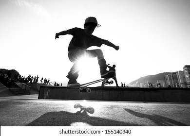 Skateboarder training on a track photographed in black and white.