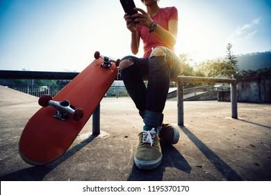 Skateboarder use mobile phone at skatepark