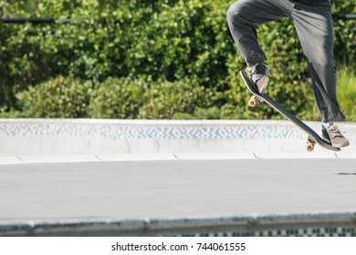 A skateboarder uses his legs and feet to execute a skateboard trick at a skateboard park
