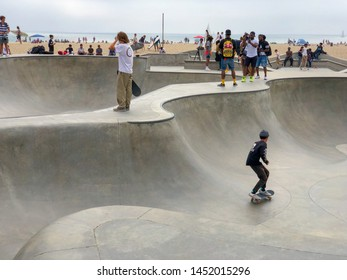 Skateboarder at Venice Beach skate park pool with crowd watching them. Famous tourist attraction at Venice Beach, California, USA. 07/13/2019