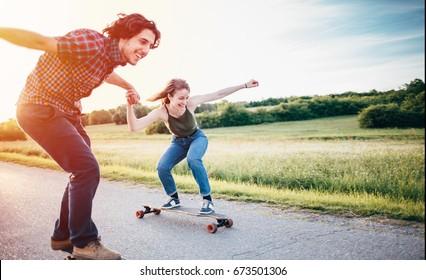 Skateboarding couple having fun/ Couple enjoying and skateboarding at nature