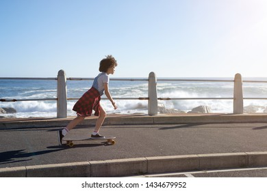 Skateboarding girl with afro riding longboard relaxing leisure summer holiday lifestyle