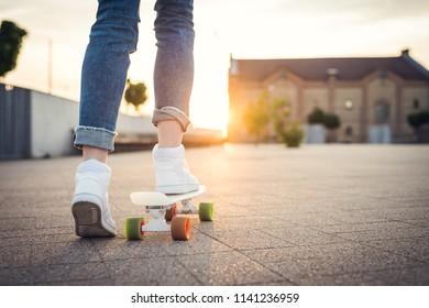 Skateboarding. Girl standind on the skateboard. Ready to ride.