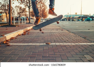 Skateboarding. A man does an Ollie stunt on a skateboard. Board in the air. Close-up of legs. Street on the background