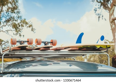 Skateboards and surfboard attached to the top of roof rack of vintage van