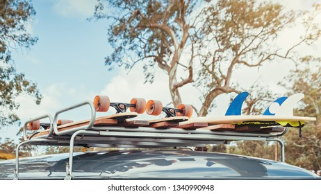 Skateboards and surfboard tied up on top of roof rack of vintage van