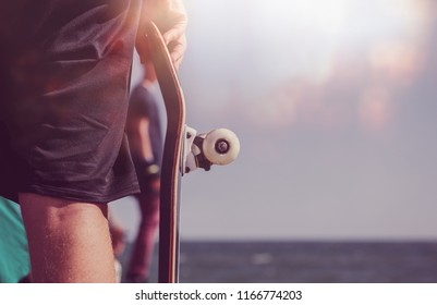 Skater boy holds skateboard in hands. Extreme sports for young and active people. Cool and popular sport for teenagers. Skateboarder holding wooden deck