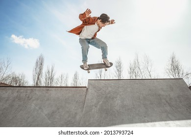 Skater boy jumps on a skateboard in a skatepark performs a difficult, dangerous trick focused on his jump