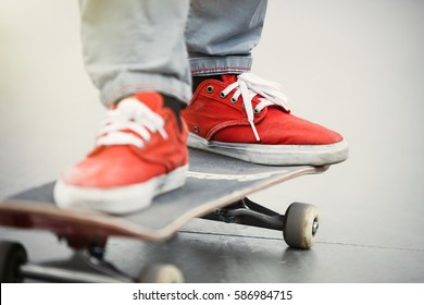 Skater boy ride on skateboard in skate park outdoor.Orange foot wear shoes on skate board deck.Skateboarding is popular & fun extreme sport for young active people.Teen lifestyle