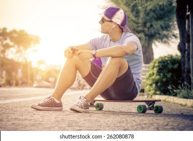 skater boy sitting on his longboard and listen to music
